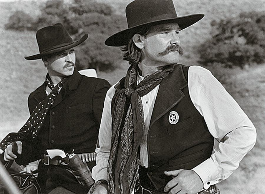 Val Kilmer & Kurt Russell in Tombstone 1993 earned a cult following as flashy, yet historically-dressed gunmen, even though the film did moderate box office.