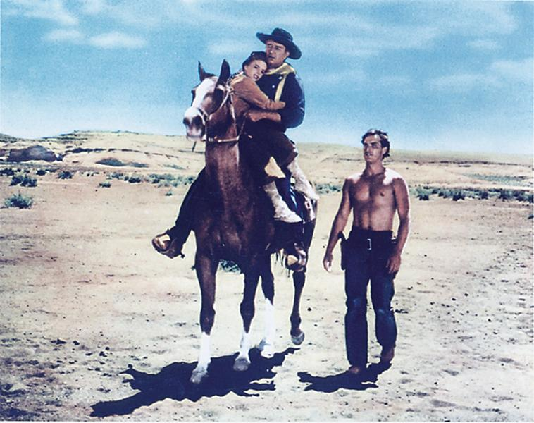 Carrying Natalie Wood in his arms, John Wayne, with Jeffrey Hunter walking, returns home.