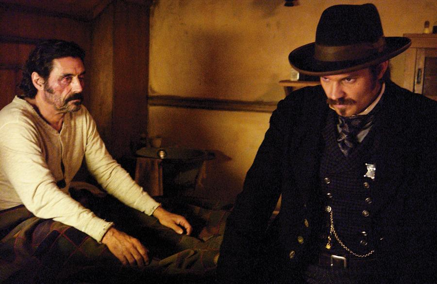 In HBO's Deadwood, Al Swearengen (played by Ian McShane) rouses the sheriff's (Seth Bullock, played by Timothy Olyphant) sense of moral justice to stand united against corrupt elements from Yankton.– Courtesy HBO Deadwood / By Preshant Gupta –