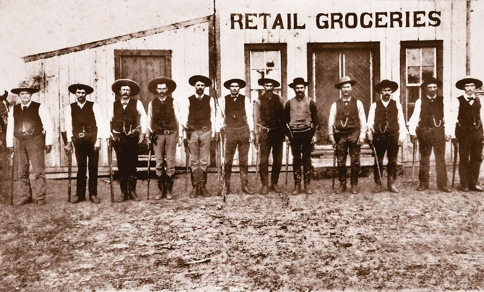 A dozen Texas Rangers line up in front of a grocery store in Cotulla on February 16, 1887. At least four of them are wearing V-topped boots.