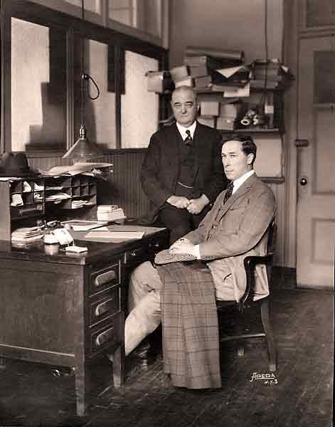 "William S. Hart sits at Bat Masterson's desk in The New York Morning Telegraph office on October 7, 1921. (Masterson died 18 days later, while working at this desk.) Masterson, standing behind the actor, had left his days as a frontier lawman far behind him to become one of the nation's top sportswriters. So famed was Bat in sporting circles that his good friend Damon Runyon based his short story character Sky Masterson on him. That character was in turn immortalized on the Broadway stage and in the movie version of Guys and Dolls. ""I play the hero that Masterson inspired,"" Hart declared. ""More than any other man I have ever met, I admire and respect him.""– Courtesy William S. Hart Collection, Los Angeles County Museum of Natural History –"