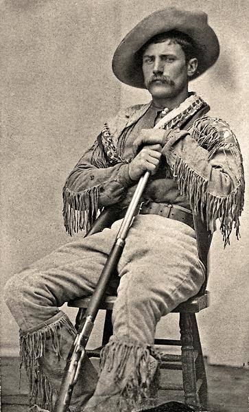 Shown at Fort Walsh, the North West Mounted Police outpost, in 1881, Jack Clark holds an 1873 Winchester and wears prairie attire that is in keeping with the Rocky Mountain Ranger uniform. The force often took on former policemen as civilian scouts, since many of them were intermarried with natives or Métis and thus offered valuable experience, especially during the years of Sitting Bull's Sioux exile in the Cypress Hills. The Mounties wore prairie dress known as mufti so as to save wear and tear on their scarlet uniforms required for official occasions. Prairie dress was often adorned with official accoutrements, such as belts, striped breeches, insignia buttons or scraps of scarlet uniform material. Courtesy Provincial Archives of Alberta A.19402