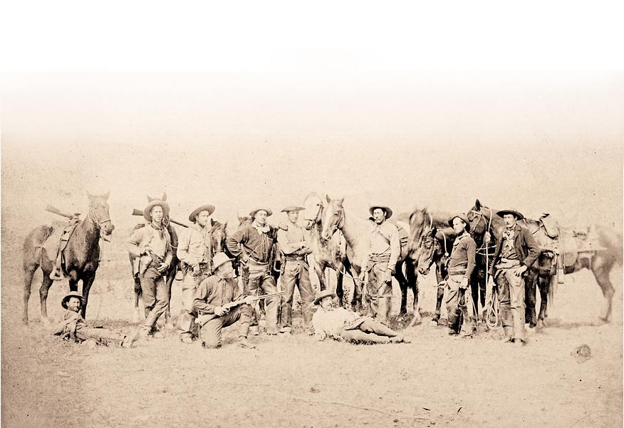 A Rocky Mountain Rangers scouting party, in the Cypress Hills during the North West Rebellion, gives their horses a well deserved rest. The Rangers utilized a varied range of weaponry and mostly provided their own sidearms, as holstered in this photo. Rifles issued, however, were uniform with regulation arms of the North West Mounted Police either single shot Snider Enfield .577 military rifles cut down to carbines, or the newer issue Winchester Model 1876 .45-75 repeating carbine, carried by the Rangers in this photo. One exception is the 1873 Winchester brandished by the kneeling Ranger at left foreground. Winchester carbines can be seen mounted in pommel holsters on the horses in the background. Courtesy Esplanade Archives 0404.0012