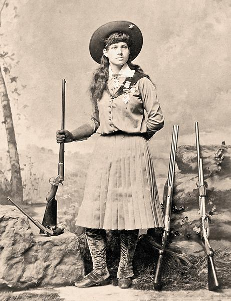 Annie Oakley, who earned worldwide notoriety for her shootist skills while touring with Buffalo Bill's Wild West, holds a Stevens tip-up target rifle and displays three of her arena guns—a double-barreled shotgun, a Spencer slide-action shotgun and a long-barreled Stevens pistol—in this circa 1886 cabinet card.– Courtesy Heritage Auctions, December 11-12, 2012 –