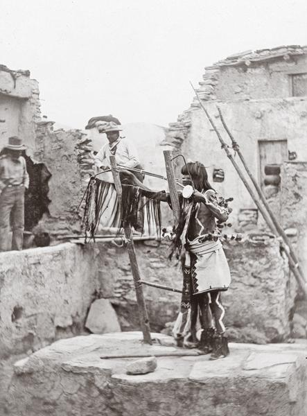 Antelope PriestDuring an 1898 Snake Dance, tourists watched Antelope priest Nihapooma remove a natchi, a ceremonial bow fastened with skins of the weasel, from a ladder in an Antelope kiva in the Hopi village of Walpi, Arizona. George Wharton James, who took this photo, wrote that, just like the weasel works himself out of a hole after being chased into another hole, the Hopi were praying for clouds to come out so rain would fall.– Courtesy Library of Congress –