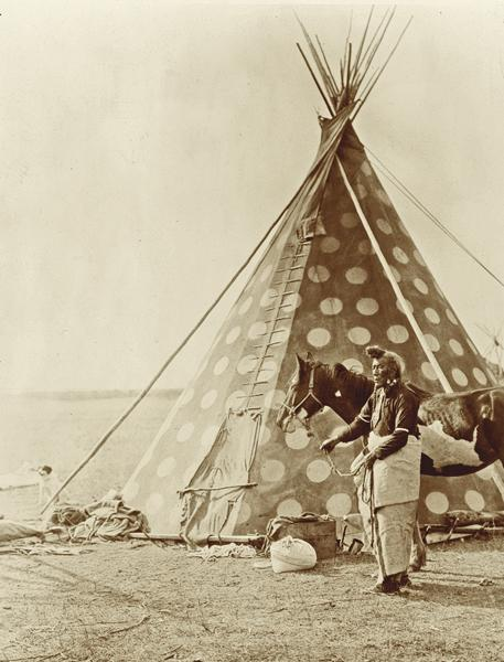 Visiting Blackfoot Brothers in MontanaBorn in 1859, spiritual healer Bear Bull had left Canada to visit his Blackfoot tribal brothers, the Southern Piegan, in Montana, in 1899. Edward S. Curtis photographed the man at the Sun Dance, and that is possibly when he captured this image of Bear Bull in front of a tipi.– Courtesy Library of Congress –