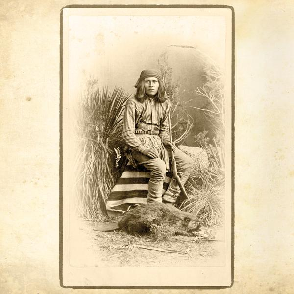 """ChahWith his gunbelt, rifle and stuffed beaver pelt, this Warm Springs Apache came to be known as Chah—Apache for """"beaver""""— due to this 1885 photo by Ben Wittick.– Courtesy Library of Congress –"""