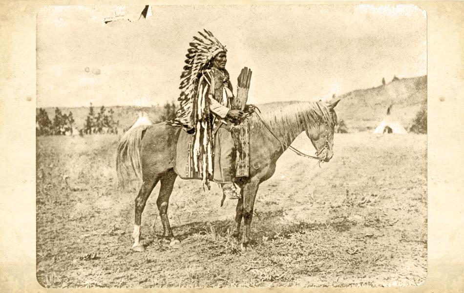 Reservation IndianThe Colville Indian Reservation agency physician since 1890, Edward Latham took up residence in Nespelem, Washington, and took hundreds of photographs of reservation Indians, including this one of Coolcoolaweela, an Okanagan man clothed in ceremonial garb.– True West Archives –