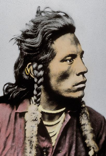 Curly in ColorSomeone has hand colored this circa 1885 photograph taken by David F. Barry. Curly, a Crow scout who assisted George Custer during the Sioux Wars, wears the traditional fur-wrapped braids and tiered shell necklace with a trade shirt.– True West Archives –