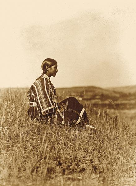 """Piegan DaydreamsEdward S. Curtis first visited the Piegan in their Montana camp during the summer of 1898. He labeled this 1910 photo of a Piegan woman """"Day-Dreams."""" With only about a few hundred left at the time of his visit, she may have been thinking of when her people were proud hunters who roamed a vast domain.– Courtesy Library of Congress –"""