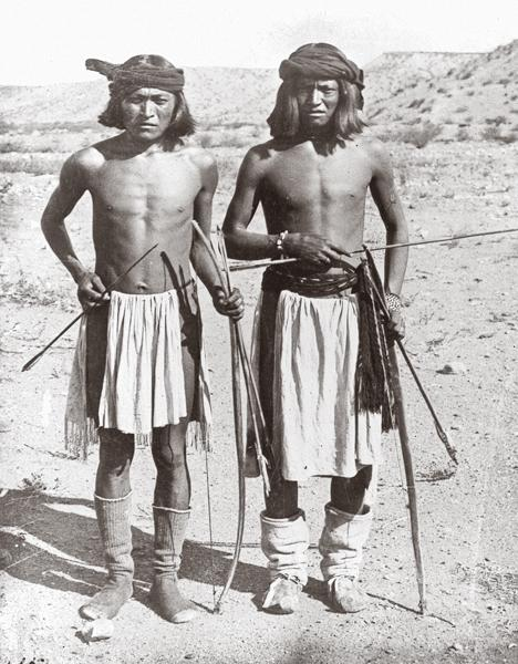Apache HuntersCarrying bows and arrows, these two Apache Hunters were photographed in 1888 by A. Frank Randall. The hunter at far left doesn't have foot gear as nice as his partner's; he wears what looks to be U.S. Army-issued socks.– Courtesy Smithsonian Institute Bureau of American Ethnology –