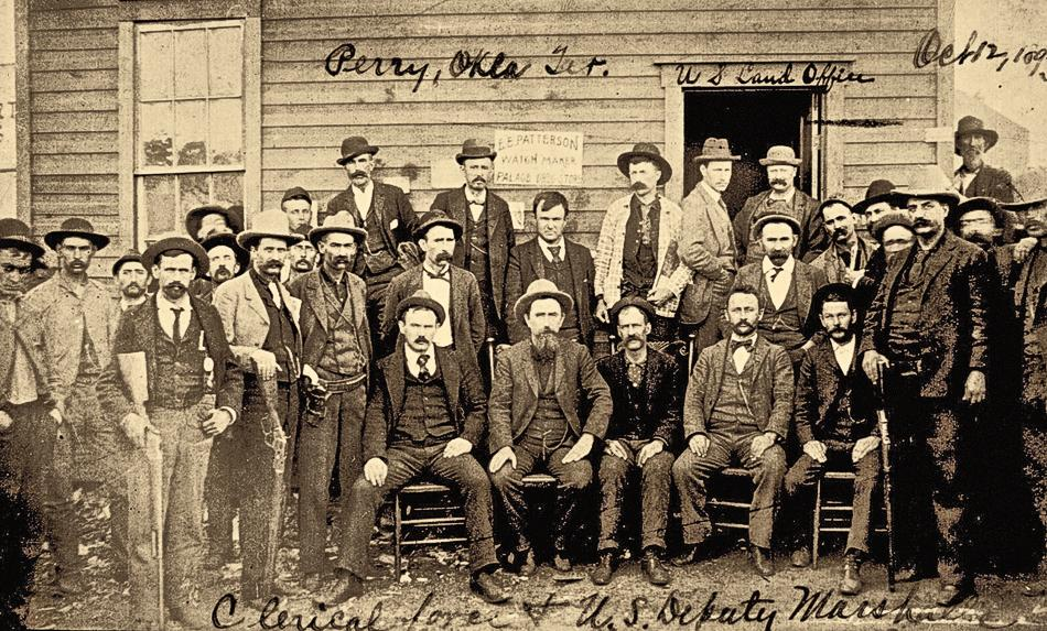 The federal deputies Judge Isaac Parker sent out to capture the lawbreakers in the 1890s included these marshals, posing in front of  a land office in Perry, Oklahoma, in 1892. Bruce faced against men with similar dress and weaponry in his 1897 shoot-out. Unless you saw the badge, these marshals looked like pretty much everyone else you encountered in those days.– Courtesy Susan Swain Peters collection, Oklahoma Historical Society –