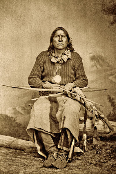 Famed Kiowa Chief Satanta, present at both famous Adobe Walls battles, in 1864 and 1874, holds his bow, bow case and quiver, made of animal hide trimmed with fur and trade cloth. This circa 1870s photo also shows metal trade arrowheads. Satanta not only led many attacks against settlers, but also helped negotiate the Medicine Lodge Treaty in October 1867. – Courtesy Phil Spangenberger Collection –