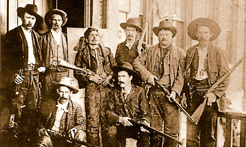 """This grizzly photograph shows the posse that brought outlaw Ned Christie to justice. In it, they pose with Christie's dead body on a board, holding his 1873 Winchester rifle. With the exception of one man, the posse members are all armed with '73 and 1886 Winchesters, and a couple appear also to be packing 1873 Colt Peacemakers. The seated man in the foreground at left holds a .45-70 single-shot 1873 Springfield """"trapdoor"""" rifle—which, despite its lack of rapid fire, boasted one heckuva wallop at long range. – True West Archives –"""