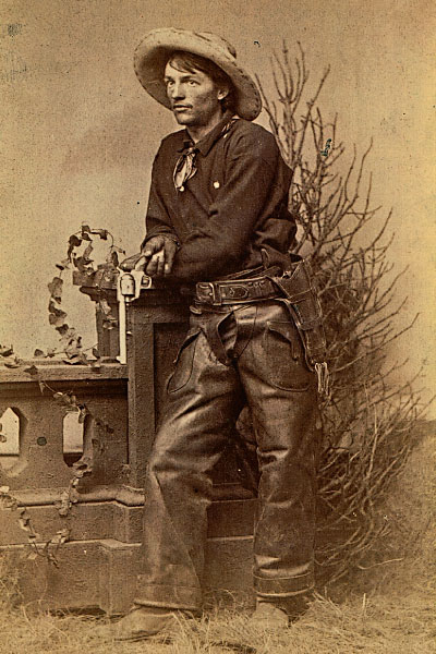 Genuine and Unknown Most historical cowboy photos record unknown individuals who posed in studio shots that reflected their pride in the lifestyle. Showing one Colt Single Action in his hand and another holstered, this typical cowboy is decked out in genuine cowboy boots, chaps, hat, bandanna and holster. – Courtesy Robert G. McCubbin Collection –