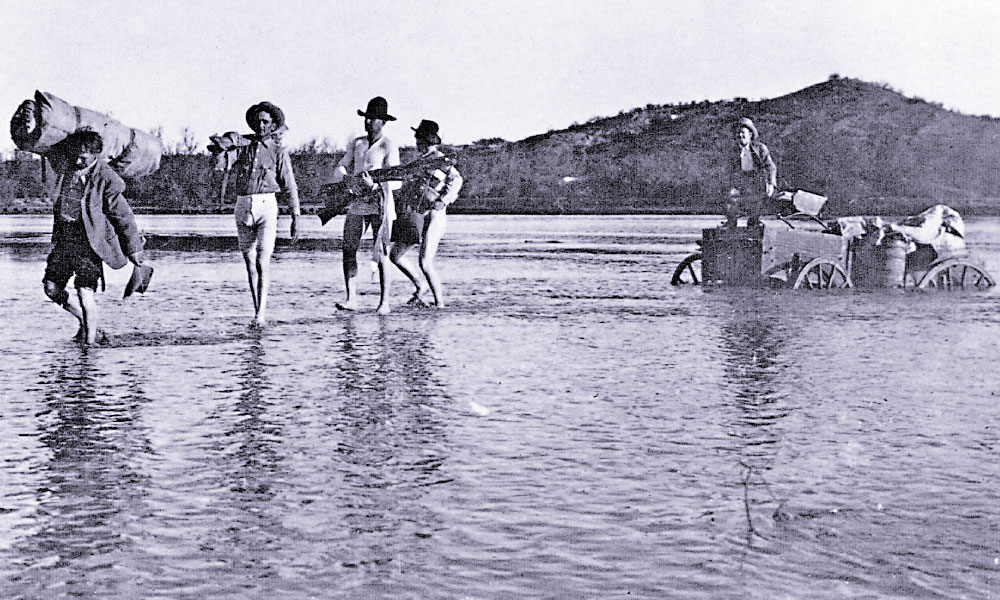 "80 Dry Bedrolls A crew of cowboys stripped to their long johns to help their ""cookie"" save their bedrolls and food from being lost to the rising waters and shifting sands of a tricky river crossing. – True West Archives –"