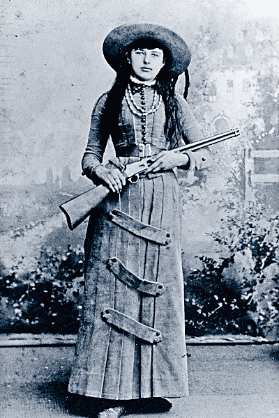 This lass (above) is dressed in the latest fashion—for the late 19th century, that is—including her then-high-tech Colt Lightning pump-action carbine. Like other trick and fancy Wild West show sharpshooters, she'll undoubtedly wow the crowd with her rapid-fire sharpshooting skills. – Courtesy Herb Peck, Jr. Collection –