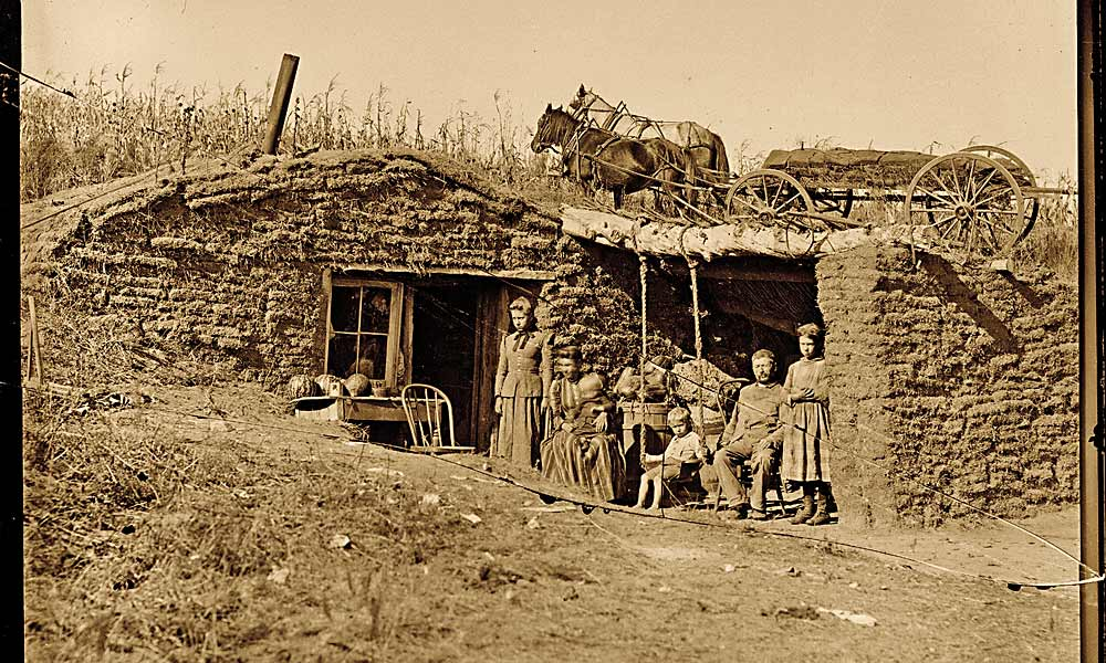 Emigrants to the treeless plains of Nebraska had to build their first homes from blocks of sod cut from the prairie. In 1892, a family posed for traveling photographer Solomon D. Butcher next to their humble abode on the South Loup River, near Virge Allen Homestead in Custer County. – Solomon D. Butcher/ Library of Congress –