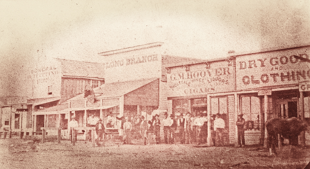 Thirsty customers paused from drinking and gambling to pose in front of Chalk Beeson's Long Branch Saloon and George M. Hoover's Bar, on Dodge City's infamous Front Street. – True West Archives –