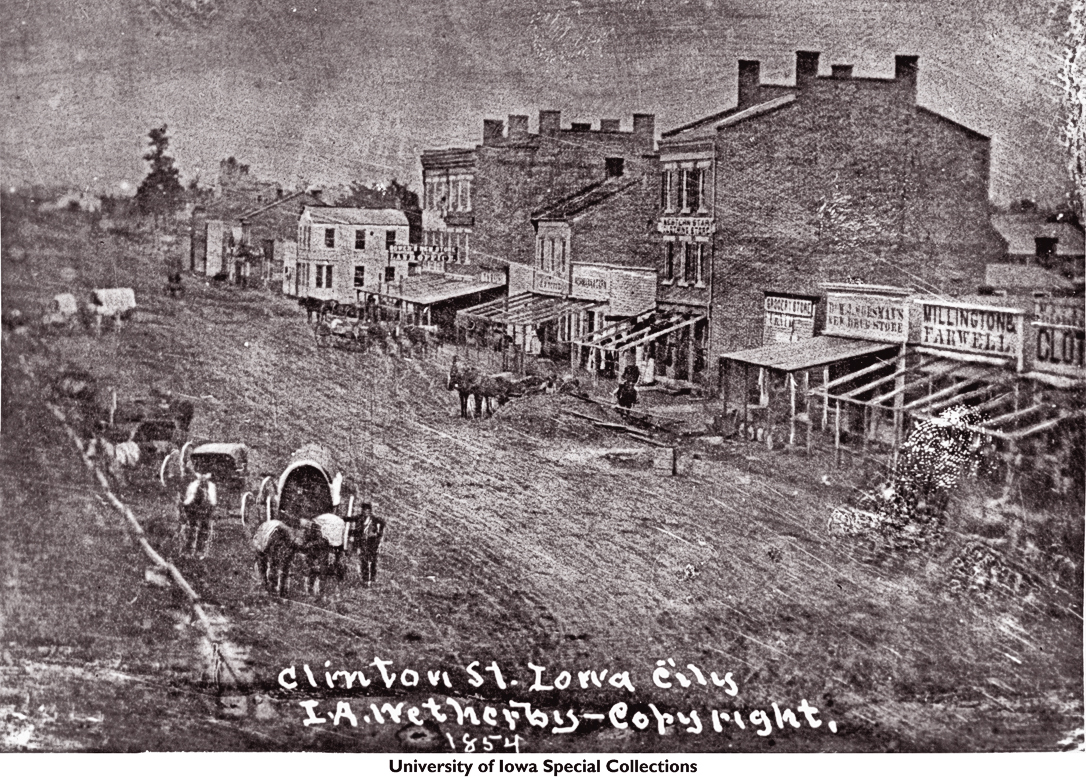 RR_IA-IowaCityHorsedrawn_wagons_outside_Clinton_St_businesses_Iowa_City_Iowa_1854-UIASC_scaled