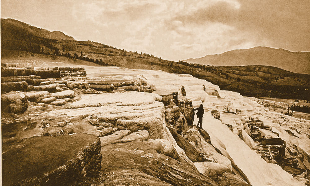 BOW_AC_HSS-Plate-III-White-Mountain-Hot-Springs-group-of-upper-basins,-Thomas-Moran,-center,-stands-on-ledge-along-upper-terraces-of-present-day-Mammoth-Hot-Springs_scaled