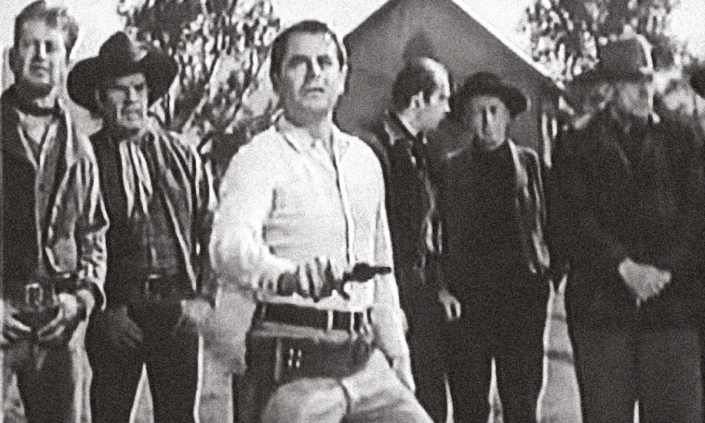 Perhaps the earliest use on film of the so-called sideways grip, although it wasn't referred to as the gangster grip until several decades later, was in the 1956 western movie, The Fastest Gun Alive. In it, in order to impress the local townsfolk of his speed and skill, star Glenn Ford quickly swipes his Colt across his cartridge belt, using this sideways hold, cocking the hammer against the belt as he makes his draw and fires his Colt. – Courtesy MGM –