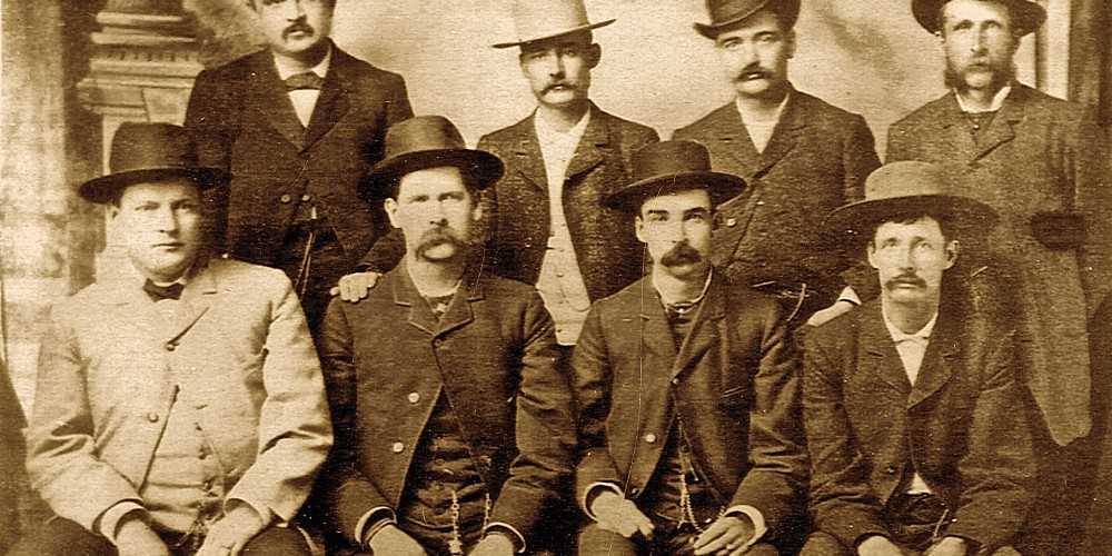 """Most likely due to their affinity as sporting men, Luke Short and Bat Masterson stand directly behind Frank McLean. The Dodge City Peace Commission photograph shows (standing, from left) William H. Harris, Short, Masterson,  William F. Petillon (seated, from left) Charles E. Bassett, Wyatt Earp, McLean and Cornelius """"Neil"""" Brown. – Courtesy Robert G. McCubbin Collection –"""