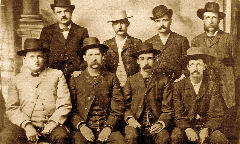 "Most likely due to their affinity as sporting men, Luke Short and Bat Masterson stand directly behind Frank McLean. The Dodge City Peace Commission photograph shows (standing, from left) William H. Harris, Short, Masterson, William F. Petillon (seated, from left) Charles E. Bassett, Wyatt Earp, McLean and Cornelius ""Neil"" Brown. – Courtesy Robert G. McCubbin Collection –"