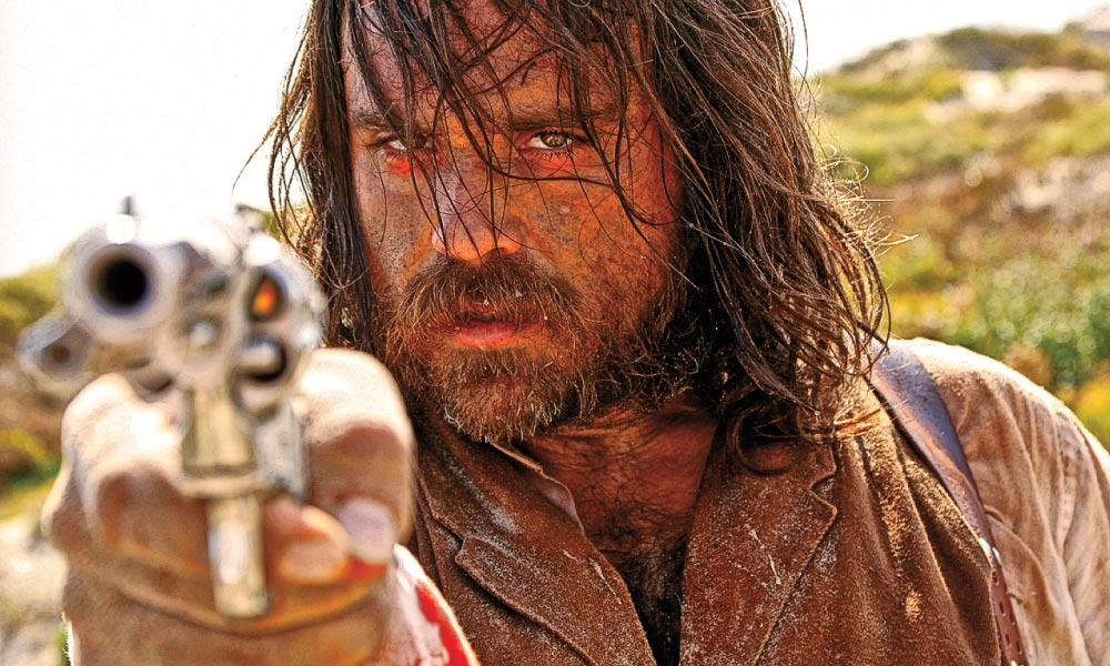 """Jim Jarmusch's 1995 otherworldly Western Dead Man, starring Johnny Depp, and Charles B. Pierce's Boggy Creek movies inspired the Horror Western Kill or Be Killed, starring Justin Meeks (above) as Claude """"Sweet Tooth"""" Barbee, a vicious gang leader searching Texas for buried gold. – Courtesy Archstone Distribution –"""