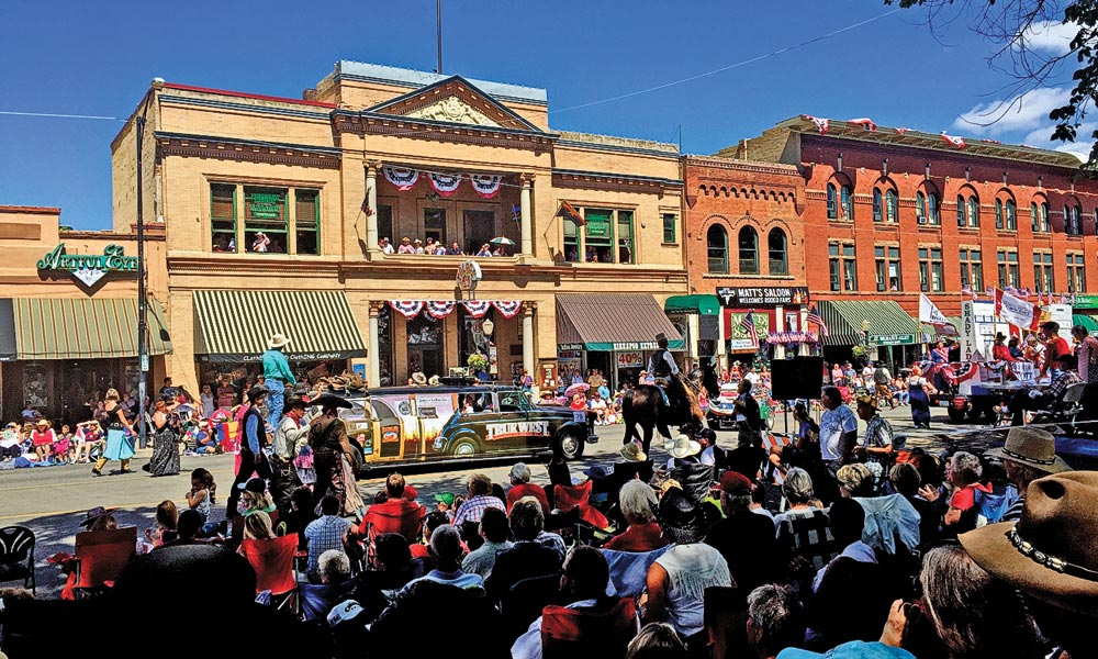 Riding where Doc Holliday strode, True West's Bob Boze Bell waves to the Prescott Frontier Days Parade crowd at the Courthouse Square and on Montezuma Street in front of the Palace Saloon, a centerpiece of Whiskey Row since its original incarnation as the Cabinet Saloon in 1874. – Stuart Rosebrook –