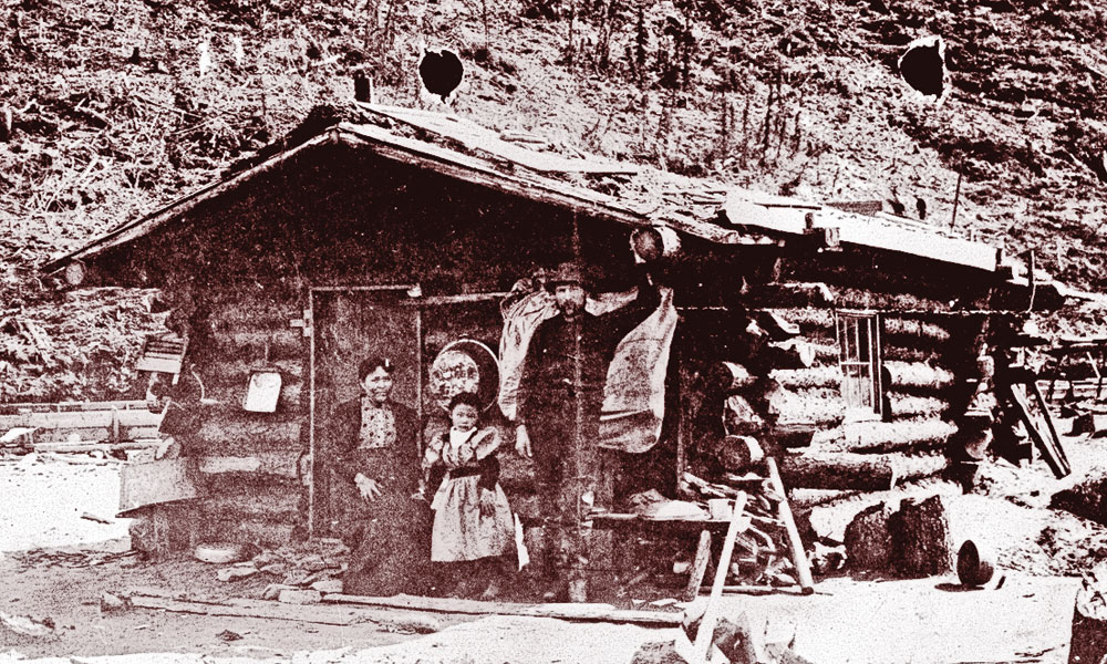 A hike on the Chinook Trail by Alaskan author Deb Vanasse inspired her to write Wealth Woman: Kate Carmack and the Klondike Race for Gold, chronicling the story of Carmack (far left), her daughter, Graphie, and husband, George, seen here at their Bonanza Creek cabin in 1897. – Courtesy Yukon Archives, James Albert Johnson fonds, 82/341, #15 –