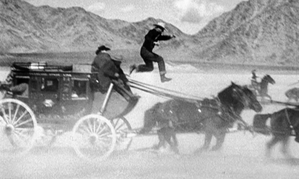 Yakima Canutt is shown in one of his most famous stunts from Stagecoach, doubling for John Wayne's Ringo Kid as he jumps to steer a team of horses after the reins have fallen from wounded stage driver Buck's hands.