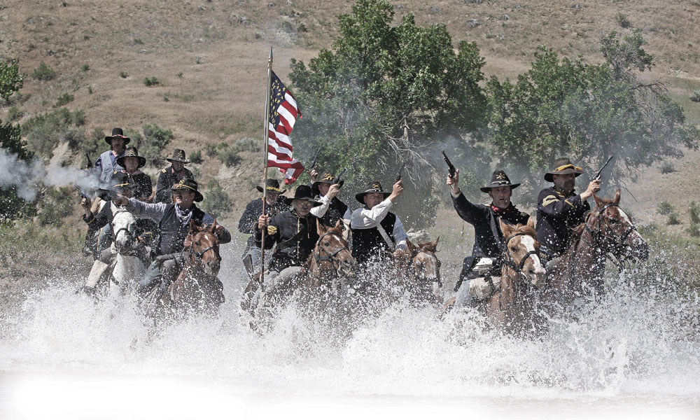U.S. Cavalry school graduates charge across the Little Bighorn  River in the Little Bighorn Battle Reenactment on the Custer Battlefield, Montana.  – Diana Volk –